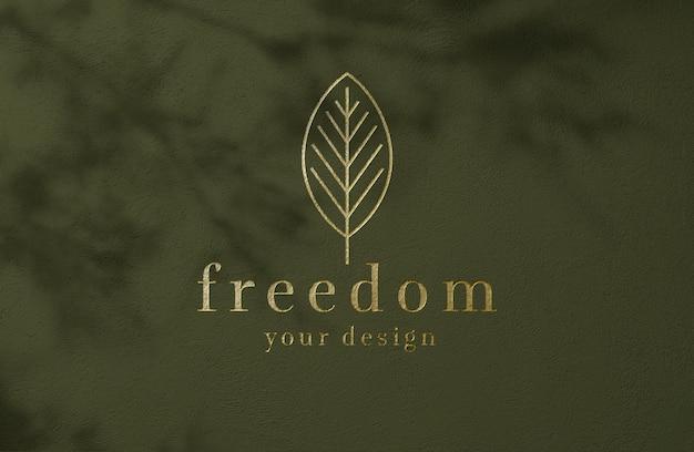 Maquete de logotipo dourado de luxo na parede de superfície verde