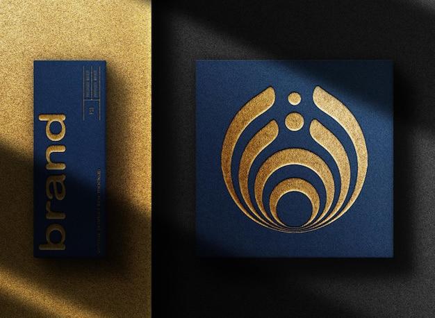 Maquete de logotipo dourado em relevo e caixa azul com fundo preto