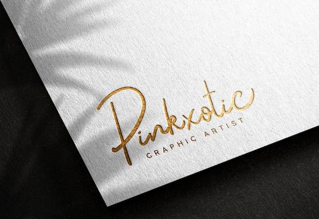 Maquete de logotipo em papel branco com efeito de impressão dourado prensado