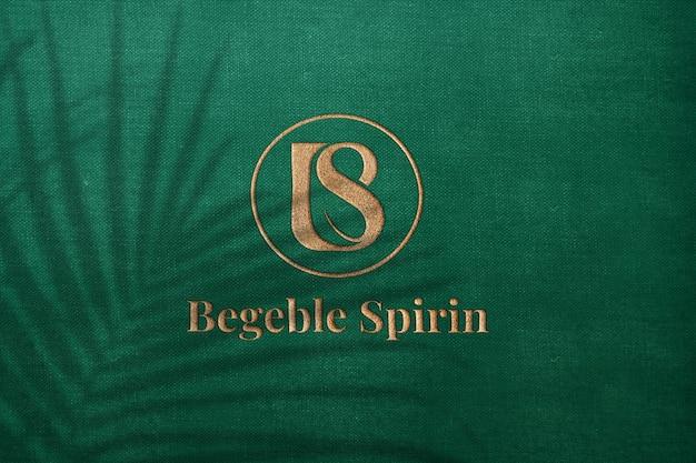 Maquete de logotipo em relevo de luxo texturizado ouro em pano verde