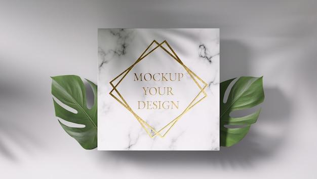 Maquete de logotipo ouro em mármore com folhas monstera