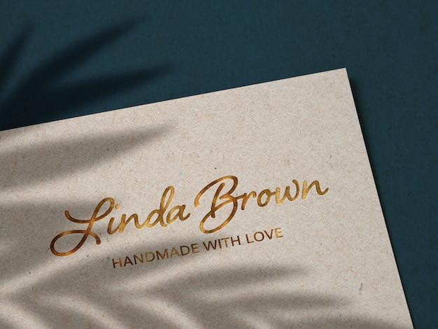 Maquete de logotipo ouro luxo em papel kraft