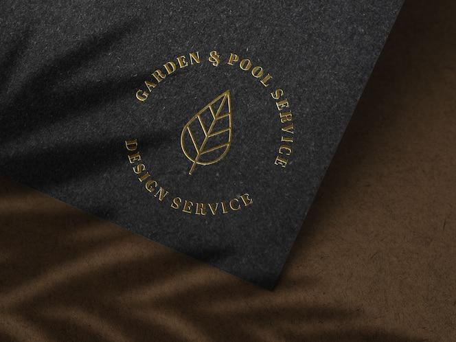 Maquete de logotipo ouro luxo na textura de papel preto