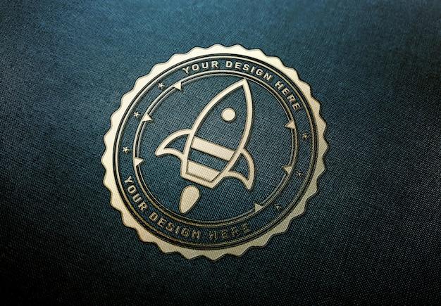 Maquete de logotipo ouro na textura de tecido escuro