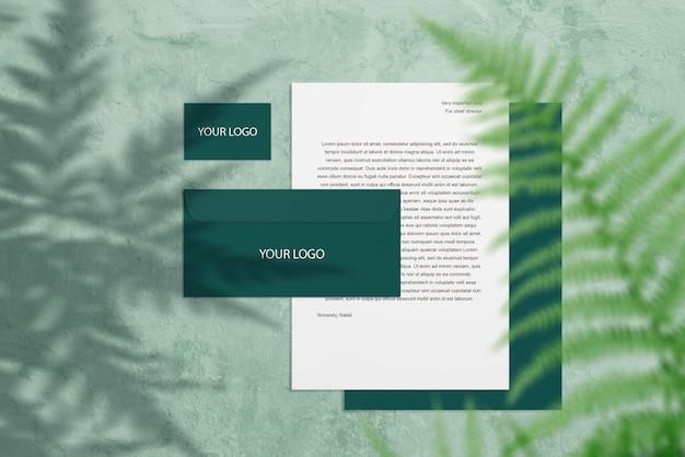 Maquete de marca com cartões verdes, carta e folha de samambaia
