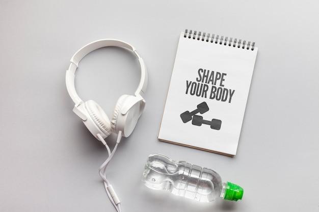 Maquete de mensagem de fitness e fones de ouvido