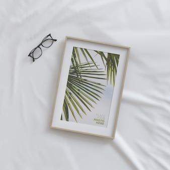 Maquete de moldura de foto com óculos na cama