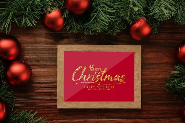Maquete de moldura de foto de feliz natal com decorações de folhas de pinheiro