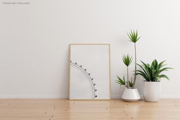 Maquete de moldura de foto de madeira vertical na sala vazia de parede branca com plantas no chão de madeira