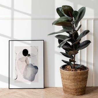 Maquete de moldura de foto por uma planta de borracha em um piso de madeira