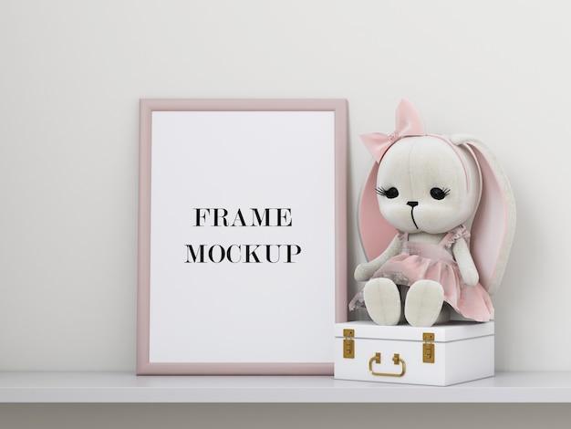 Maquete de moldura de foto rosa ao lado de brinquedo macio