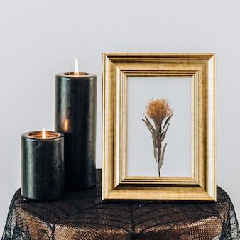 Maquete de moldura dourada perto das velas