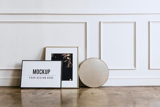 Maquete de moldura em branco por uma parede branca