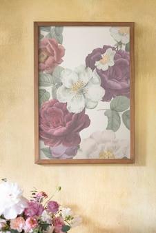Maquete de moldura floral em uma parede amarela de grunge