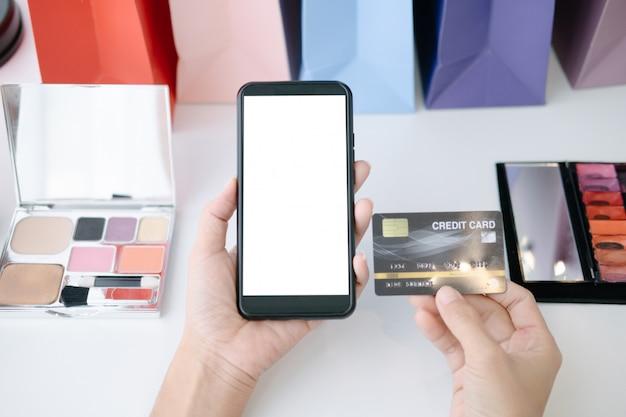 Maquete de mulher bonita, segurando o cartão de crédito, compras on-line com smartphone em sites on-line