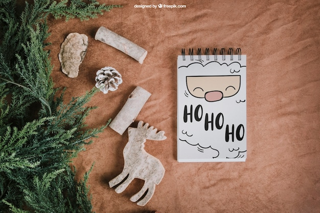Maquete de natal com bloco de anotações ao lado de abeto