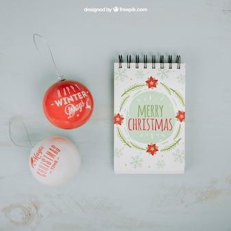 Maquete de natal com bloco de notas e bolas