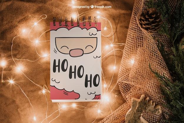 Maquete de natal com bloco de notas e luzes