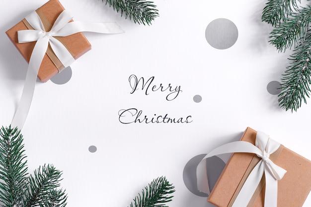 Maquete de natal com presentes de artesanato, caixa e galhos de pinheiro verde.