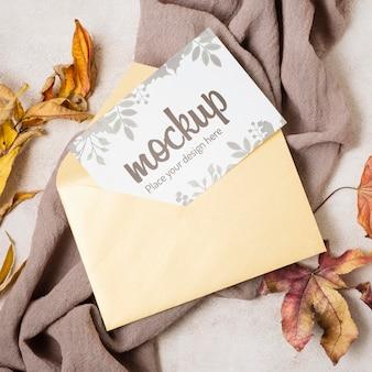 Maquete de outono plana com folhas em um pano cinza