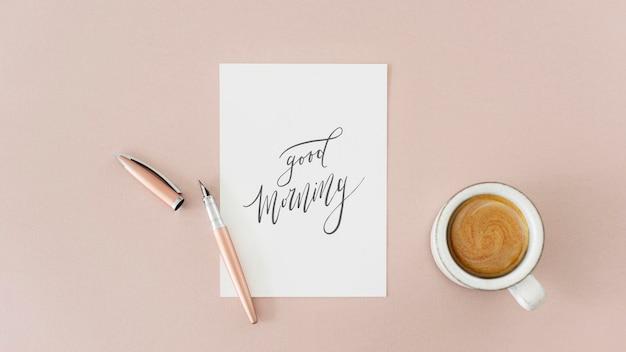 Maquete de papel branco ao lado de uma xícara de café em uma mesa rosa