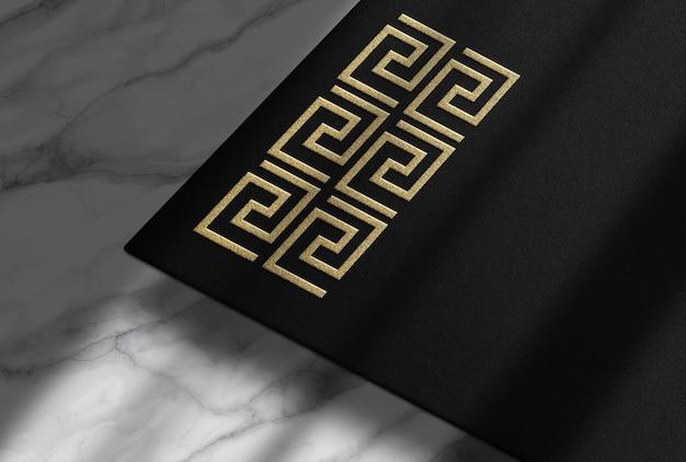 Maquete de papel preto em relevo dourado com superfície de marmer