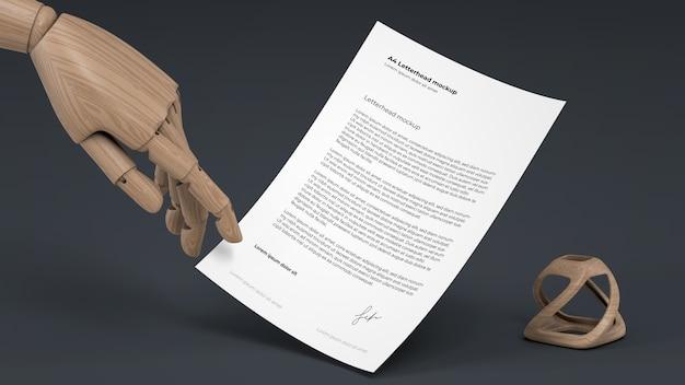 Maquete de papel timbrado com mão de fantoche de madeira