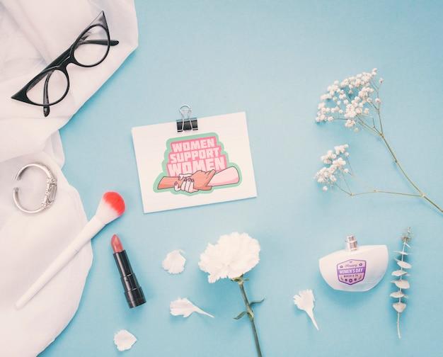 Maquete de papelão com flores e maquiagem em fundo azul