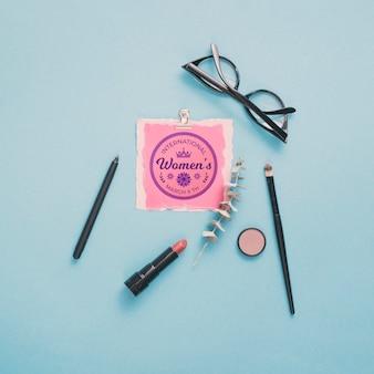 Maquete de papelão com maquiagem e óculos em fundo azul