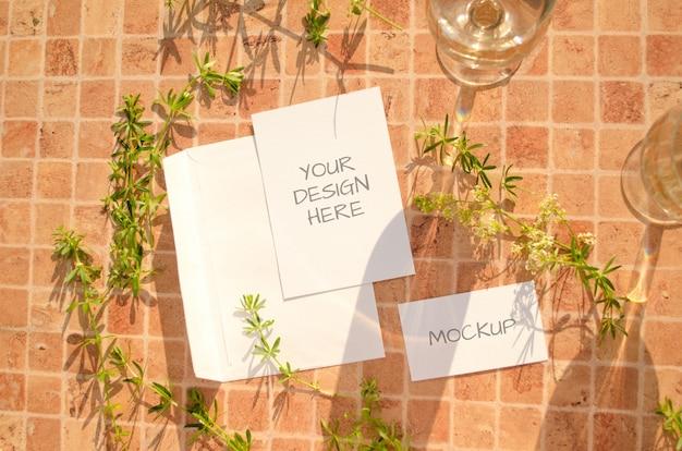 Maquete de papelaria com ervas, copos de vinho e sombras caindo sobre uma laranja pêssego