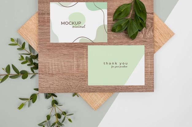 Maquete de papelaria com folhas e camada plana de madeira