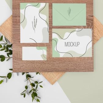 Maquete de papelaria com folhas e madeira acima da vista