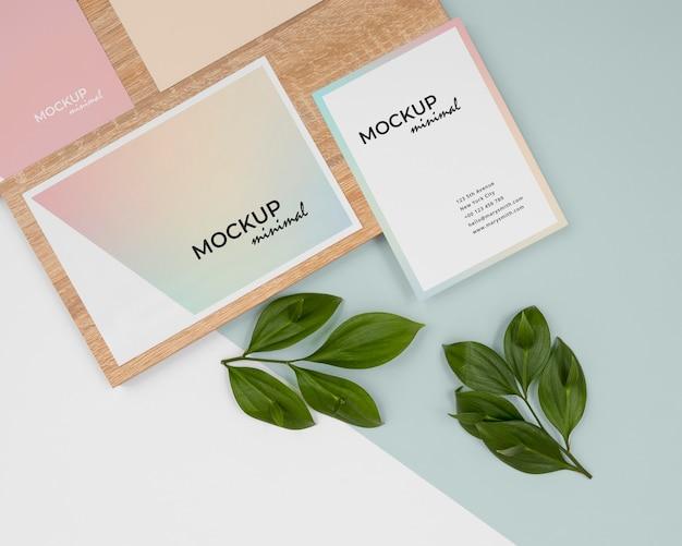 Maquete de papelaria com folhas e vista superior da madeira