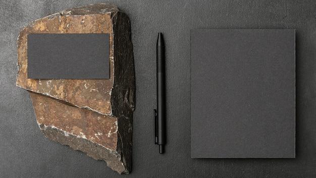 Maquete de papelaria em concreto escuro com rocha áspera