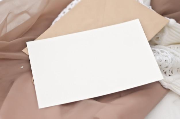 Maquete de papelaria em estilo vintage. cartão do modelo no envelope ofício para seu projeto, convites, saudações, letras ou ilustrações. as suaves cores bege e brancas. camada inteligente psd