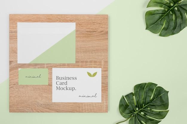 Maquete de papelaria plana com folhas e madeira