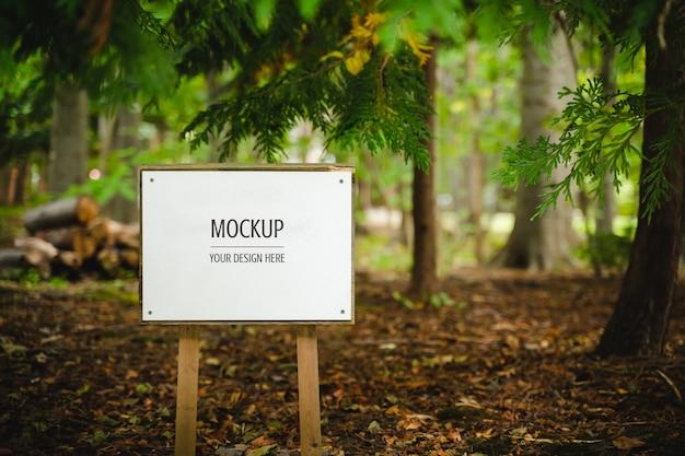 Maquete de placa de madeira branca em branco na floresta