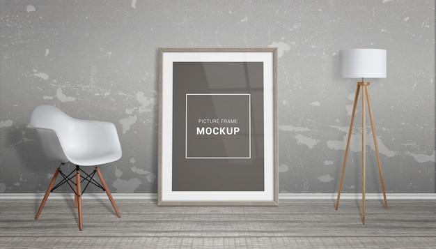 Maquete de quadro de imagem. a moldura está encostada na parede. cadeira e lâmpada ao lado. chão de madeira.