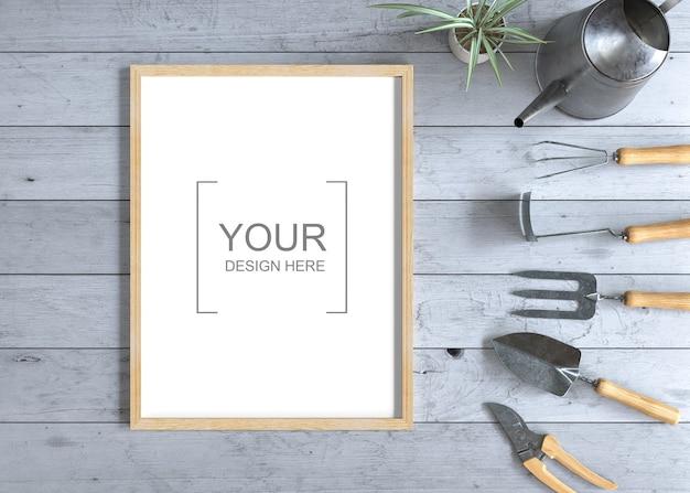 Maquete de quadro em mesa de madeira com ferramentas de jardinagem