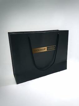 Maquete de saco de papel preto com logotipo dourado
