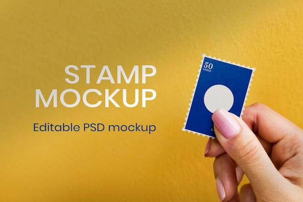 Maquete de selo postal psd em uma mão