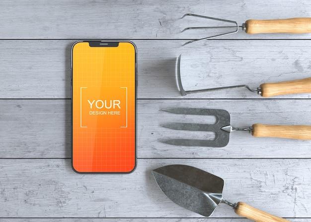 Maquete de smartphone com ferramentas de jardinagem