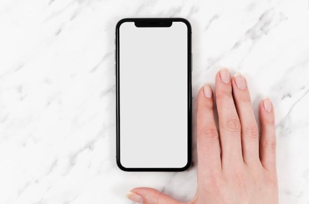 Maquete de smartphone com vista superior com a mão