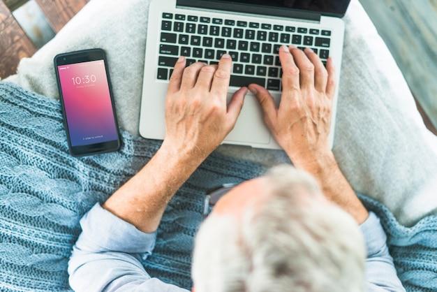 Maquete de smartphone para apresentação de app com o homem usando o laptop