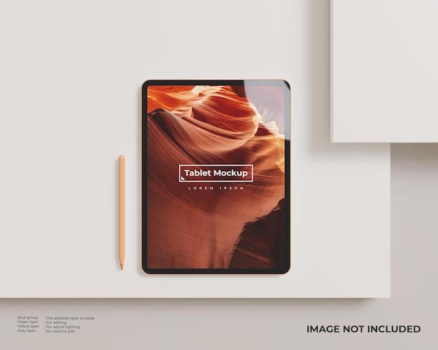 Maquete de tablet com caneta na lateral parece vista superior em superfície branca minimalista