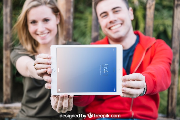 Maquete de tablet com casal ao ar livre