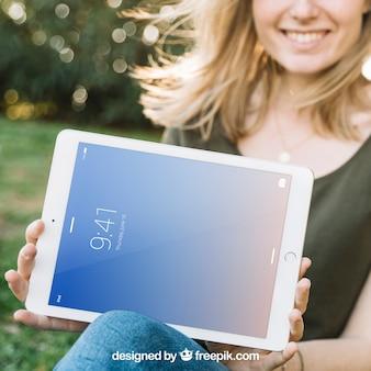 Maquete de tablet com mulher sorridente ao ar livre
