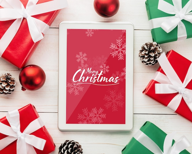 Maquete de tablet de feliz natal com decorações de folhas de pinheiro