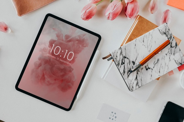 Maquete de tablet digital em uma mesa com flores