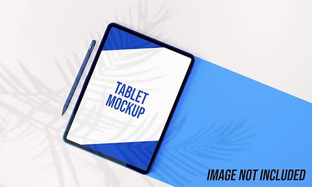 Maquete de tablet e caneta com sombra de folhas de palmeira